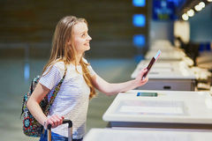 Traveler with backpack in international airport at check-in counter Royalty Free Stock Photography