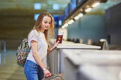 Traveler with backpack in international airport at check-in counter Stock Photos
