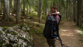 Traveler with a backpack leaned against the stone to rest stock footage
