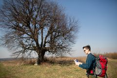 A traveler with a backpack, looking at the map and walking in the countryside. Tree in the background stock photos