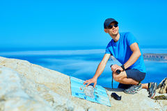 Traveler with backpack. Male traveler with backpack and map standing on the cliff against sea and blue sky at early morning Royalty Free Stock Photo