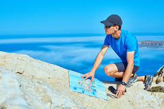 Traveler with backpack. Male traveler with backpack and map standing on the cliff against sea and blue sky at early morning Royalty Free Stock Image