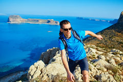 Traveler with backpack. Male traveler with backpack runs on the cliff against sea and blue sky at early morning. Balos beach on background, Crete, Greece Royalty Free Stock Photo
