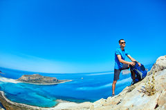Traveler with backpack. Male traveler with backpack  standing on the trail against sea and blue sky at early morning. Balos beach on background, Crete, Greece Royalty Free Stock Images