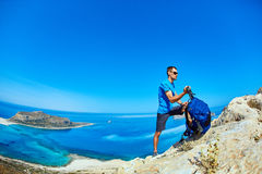 Traveler with backpack. Male traveler with backpack  standing on the trail against sea and blue sky at early morning. Balos beach on background, Crete, Greece Royalty Free Stock Image