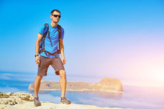 Traveler with backpack. Male traveler with backpack standing on the trail against sea and blue sky at early morning. Balos beach on background, Crete, Greece Royalty Free Stock Photo