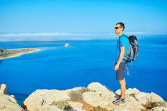 Traveler with backpack. Male traveler with backpack standing on the trail against sea and blue sky at early morning. Balos beach on background, Crete, Greece Stock Images