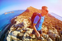Traveler with backpack. Male traveler with backpack standing on the trail against sea and blue sky at early morning. Balos beach on background, Crete, Greece Royalty Free Stock Photos