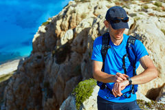 Traveler with backpack. Male traveler with backpack standing on the trail on the cliff against sea and blue sky at early morning. Balos beach on background Royalty Free Stock Images