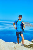 Traveler with backpack. Male traveler with backpack standing on the trail on the cliff against sea and blue sky at early morning. Balos beach on background Stock Image