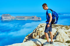 Traveler with backpack. Male traveler with backpack standing on the trail on the cliff against sea and blue sky at early morning. Balos beach on background Royalty Free Stock Image