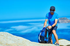 Traveler with backpack. Male traveler with backpack standing on the trail on the cliff against sea and blue sky at early morning. Balos beach on background Royalty Free Stock Photo