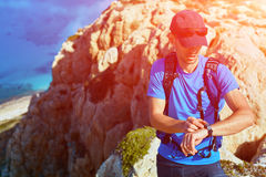 Traveler with backpack. Male traveler with backpack standing on the trail on the cliff against sea and blue sky at early morning. Balos beach on background Stock Images