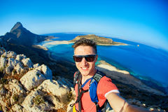 Traveler with backpack. Man traveler with backpack standing on the cliff against sea and blue sky at early morning. Balos beach on background, Crete, Greece. man Royalty Free Stock Images