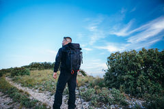 Traveler with backpack on mountain path stock photo