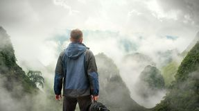 Hiker with backpack in mountains enjoying on view of foggy mount Royalty Free Stock Image