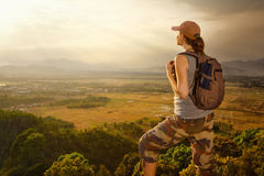 Traveler with backpack relaxing on top of mountain and enjoying royalty free stock image