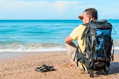 Traveler with a backpack resting on the beach near the sea. In Thailand Royalty Free Stock Photo