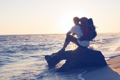 Traveler with backpack sits next to sea. Traveler with backpack sits on a snag in the surf and admires the sea during the sunset. Amazing adventure on the Stock Photos
