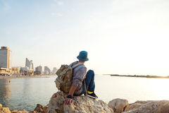 Traveler with backpack sitting on the rocks near the sea. On the beach in the city and looking far away Stock Images