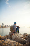 Traveler with backpack sitting on the rocks near the sea. On the beach in the city and looking far away at the horizon Royalty Free Stock Images