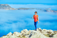 Traveler with backpack. Sporty female traveler with backpack standing on the cliff against sea and blue sky with white clouds at early morning, Crete, Greece Royalty Free Stock Photos