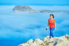 Traveler with backpack. Sporty female traveler with backpack standing on the cliff against sea and blue sky with white clouds at early morning, Crete, Greece Stock Photography