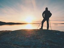 Traveler with  backpack stand on rocky shore and looking  at the sunrise.  Rocky clif. F close to horizon Stock Photos