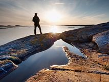 Traveler with  backpack stand on rocky shore and looking  at the sunrise.  Rocky clif. F close to horizon Stock Photo