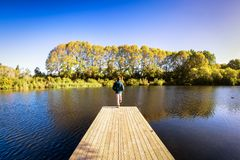A traveler with a backpack standing over the edge of a wooden boardwalk stock photography