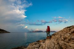 Traveler with backpack stands on the rock seashore stock images