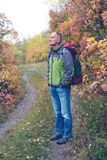 Traveler with a backpack stands, in thoughtfulness. On a forest road, among colorful foliage, on a beautiful autumn day Stock Images