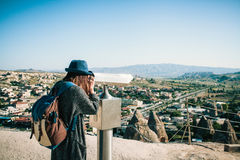 A traveler with a backpack on at viewpoint looks through binoculars at a beautiful view of the town of Goreme in Stock Image