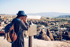 A traveler with a backpack on at viewpoint looks through binoculars at a beautiful view of the town of Goreme in. Cappadocia in Turkey. Journey Stock Photography