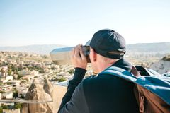 A traveler with a backpack on at viewpoint looks through binoculars at a beautiful view of the town of Goreme in. Cappadocia in Turkey. Journey Stock Photos