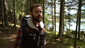 Traveler with a backpack walks through the forest stock footage
