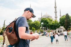 A traveler in a baseball cap with a backpack is looking at the map next to the blue mosque - the famous sight of. Istanbul. Travel, sightseeing Royalty Free Stock Photography