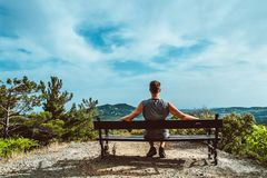 Traveler, bearded man is sitting on a bench. sunny day in the mountains. National park Troodos, Cyprus royalty free stock photography