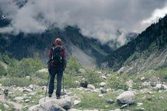 Traveler with big dog goes along mountain gorge Stock Image