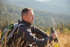 Traveler with binoculars in the mountains. A man with a binocular looks tight at a distance stock photos