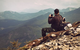 Traveler with binoculars sitting on top of a mountain. And and looks into the distance at sunset. Filtered image:cross processed vintage effect Royalty Free Stock Photos
