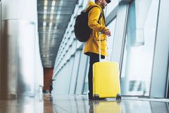Traveler in bright jacket with yellow suitcase backpack at airport on background large window blue sky, passenger waiting flight. In departure hall of lobby royalty free stock photography