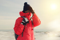 Traveler in bright winter jacket standing in a winter field. Woman traveler in bright winter jacket standing in a winter field Stock Image