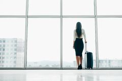 Traveler businesswoman waiting for delayed flight at airport lounge standing with luggage watching tarmac at airport window. Woman. At boarding gate before royalty free stock photos