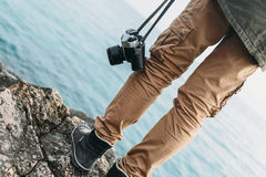 Traveler with camera standing on coast Stock Photos