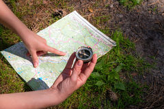 Traveler checks with the route using a map and compass. Woman traveler checks with the route using a map and compass Royalty Free Stock Photography