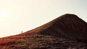 A traveler climbs a mountain. Landscape Royalty Free Stock Image