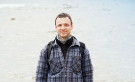 Traveler on a coast. Young adult man portrait. Traveler on Sea coast. Young adult  Caucasian man in warm outdoor clothes with backpack Royalty Free Stock Photography