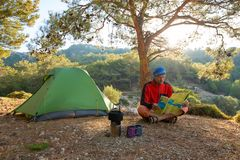 Traveler is considering a map in the mountains among lush pines. At sunny morning - camp during adventure travel along Lycian way, Turkey. Backlight stock image
