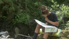Traveler Considers Map in Forest. Hipster male with dreadlocks examines paper map while traveling sitting on stone near mountain stream stock video
